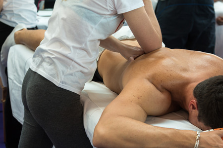 spinal adjustment: Athletes Back Professional Massage after Fitness Activity by Young Masseuse, Wellness and Sport Stock Photo