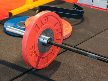 stell: Closeup of Fitness Equipment in Gym: Stell Barbell with Red Plates