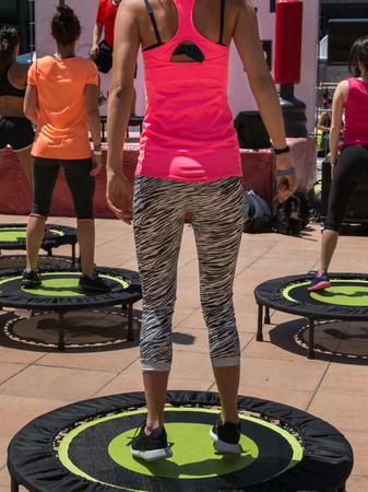 Hübsches Mädchen mit rosa Sport Mit Übung auf Rebounder