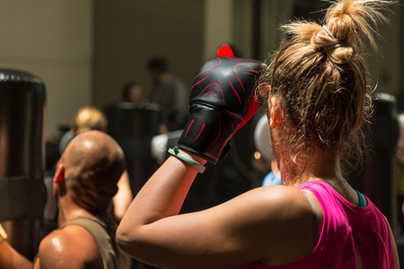 pugilist: Young Woman with Boxing Glove and Pink Sportswear in Fitness Class with Punching Bag