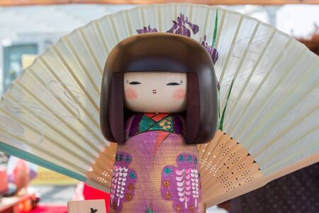 kokeshi: Traditional Japanese Wooden Kokeshi Doll and wagasa umbrella in background, Touristic Souvenir Stock Photo