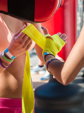 boxing tape: Close up of Young Girls Taping Her Hands in Pink Boxing Tape, Fitness Training Stock Photo