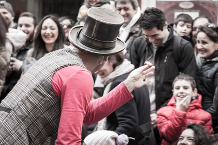 trickster: illusionist with magicians hat during street performance, rear view