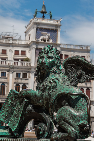 winged lion: Bronze Winged Lion Statue and Torre dellOrologio building in background in St. Marks Square, Venice, Italy