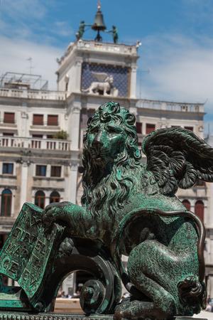 leon con alas: Le�n con alas de bronce de la estatua y Torre del Reloj construcci�n en el fondo de la plaza de San Marcos, Venecia, Italia