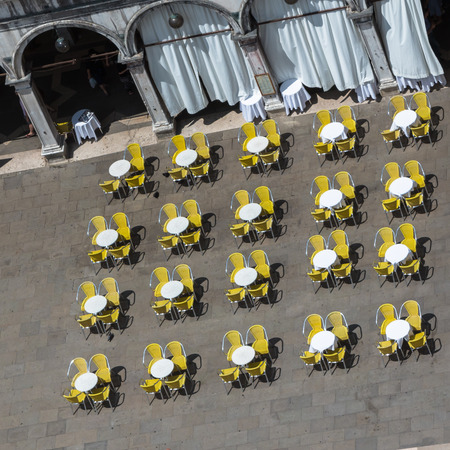 saint marks: Red and Yellow Chairs and Round Tables Aerial View on Famous Saint Marks Square in Venice, Italy