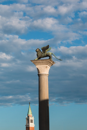 leon con alas: Columna de bronce le�n con alas en la plaza de San Marcos y San Giorgio Maggiore campanario en el fondo, Venecia - Italia