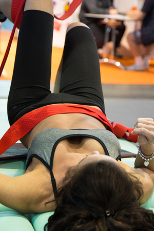traction: Closeup of Girl doing Fitness Traction Therapy on Bed with Suspension-based Exercise Training System