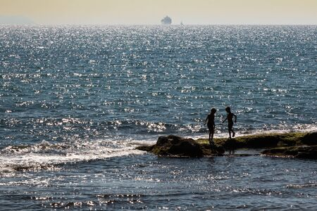 Silhouette of Two Children Playing on Reef near Sea at Sunset and Supply Ship in background