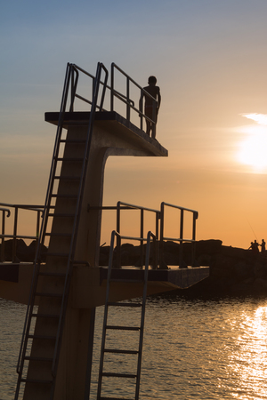Courage and Jump: Silhouette of Child Before Jumping from High Board into Water, Fun in the Summer