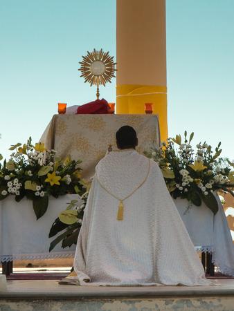 Sacerdote arrodillan delante de un altar con ostensorio de oro: Iglesia al aire libre