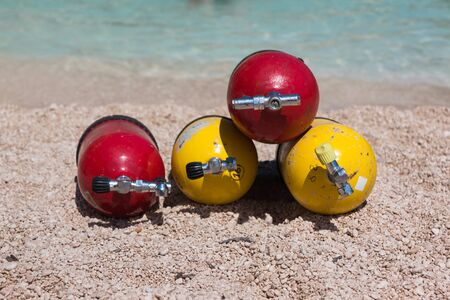 Colorful Scuba Oxygen Tanks for Divers on a Beach