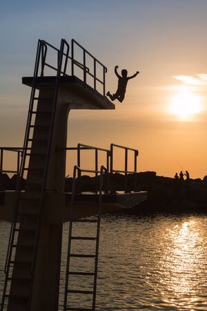 Courage and Jump: Silhouette of Child Jumping from High Board into Water, Fun in the Summer
