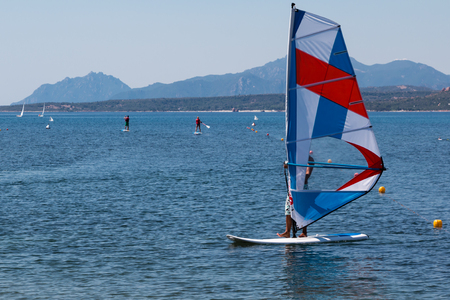 sailboard: Wind Surfing in the Summer on Calm Coastal Water, Small Island in Background