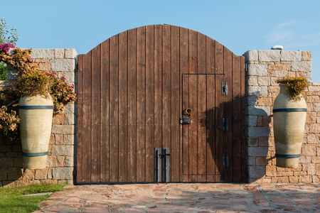 Wooden Brown Gate in Stone Wall near Ornamental Flower Vases