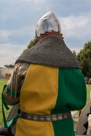 Knight with Helmet and Yellow and Green Clothes seated on a Chair: Medieval Event Reconstruction