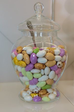 Colourful Sugared Almond inside Glass Jars on White Shelf