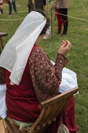 darn: Woman with Renaissance Dress Seated on Savonarola Chair doing Needlework Outdoors