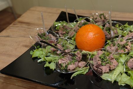 Tuna Fish Portions with Vegetable Condiment, Green Salad and Orange Fruit on Black Dish