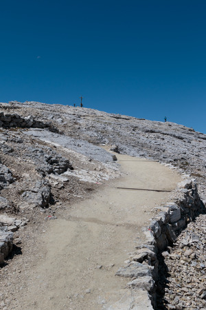 Stone Path among Barren Mountains, Wooden Christian Cross and Worshippers in Italian Dolomites Alps in Summer Time Stock Photo