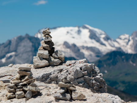 Stones Stacked One Onto Each Other and Mountain Ridge in Italian Dolomites Alps in Summer Time in Background Stock Photo