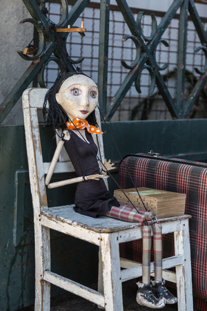 puppet master: Wooden Worn-out Woman Marionette on White Chair Stock Photo