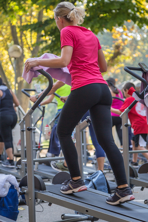 Woman in Sportswear Exercising Outdoor on Treadmill