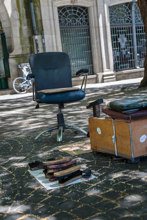 Shoeshiner Equipments in the Street: Chair, Wooden Footrest, Brushes and Shoe Polish Set Stock Photo