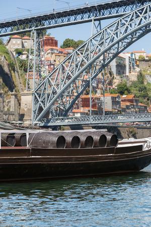 Traditionelle Rabelo Boote am Ufer des Flusses Douro und Dom Luis I Brücke im Hintergrund - Porto, Portugal
