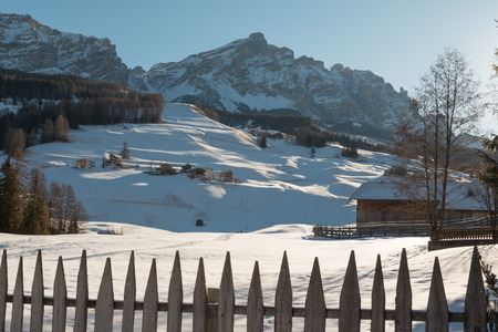 Wooden Fence, Houses and Mountains with Snow in Europe: Dolomites Alps Peaks for Winter Sports Lizenzfreie Bilder