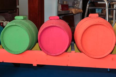 Antikes Fass in fluoreszierenden Farben: Orange, Pink und Grün