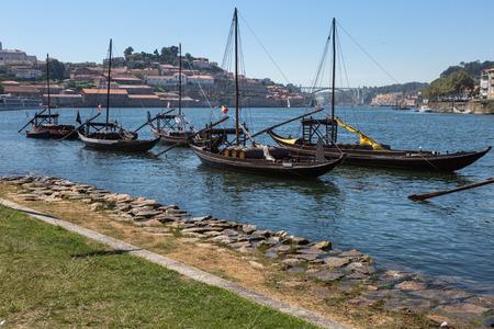 Typische Rabelo-Boote am Ufer des Flusses Douro und Vila Nova de Gaia im Hintergrund - Porto, Portugal Lizenzfreie Bilder