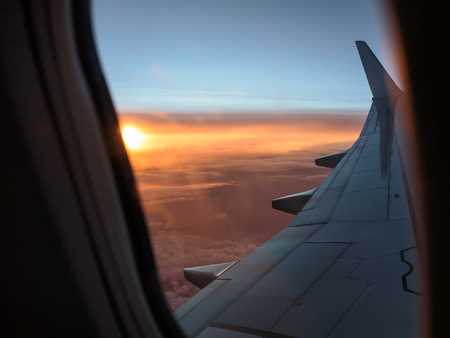 Looking Outside a Window of an Aircraft Cabin: White Airplane Wing and Sunset over the Clouds Lizenzfreie Bilder