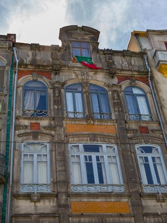 Typisch bunte portugiesische Architektur: Fliesen Azulejos Fassade mit antiken Fenstern und Balkon - Portugal