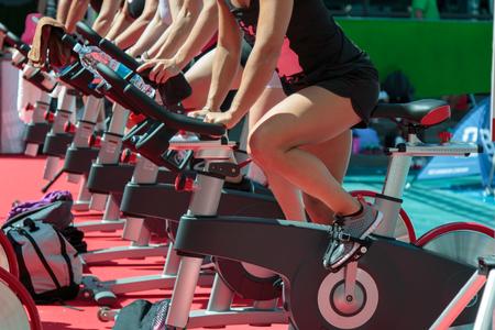 Gruppe von Jungen und Mädchen in der Turnhalle: Workout mit Spinning Bikes