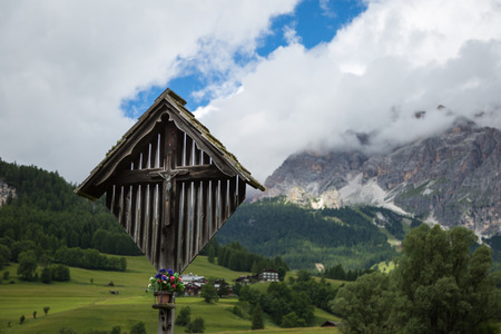 Wooden Christian Cross and Italian Dolomites Alps in Background in Summer Time