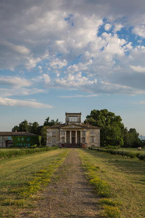 Ancient Italian Neoclassical House inside Park and Blue Sky with Clouds.