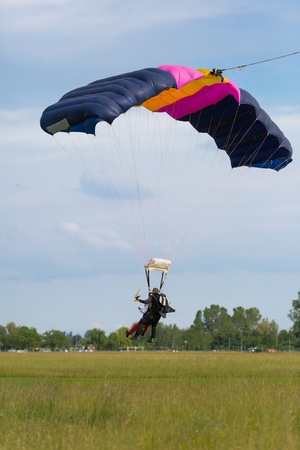 Parachutists: Instructor and Beginner with Blue Parachute preparing for Landing