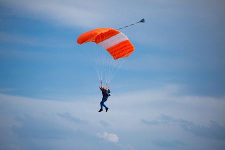 Parachutist with Orange Parachute against Blue Sky preparing for Landing