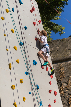 Ten Years Boy Climbing Outdoor Artificial Wall with Modern Colorful Holds.