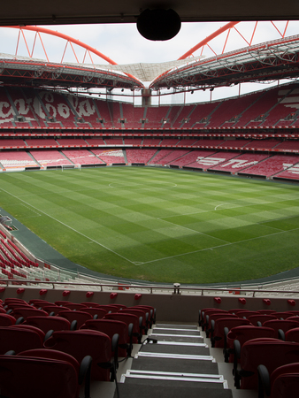 View of Da Luz Stadium: Red Empty Seating and Green Soccer Pitch - Lisbon, Portugal.