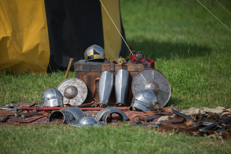 Helmets, Shields and Medieval Metallic Armors and Weapons, Outdoors near Tent.