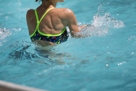 Woman Doing Water Aerobics in an Outdoor Swimming Pool: Rear View.
