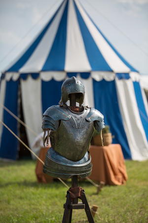 Medieval Metallic Armor and Ancient Tent in background.