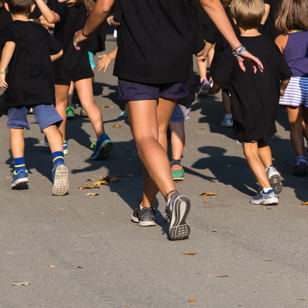 Children with Black Shirt Running in the Park with Young Teacher.