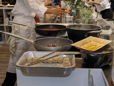 Cooking inside Restaurants Kitchen, Pans and Chef with Uniform.