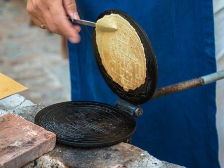 Preparing Little Crepe on Circular Cooking Plate.