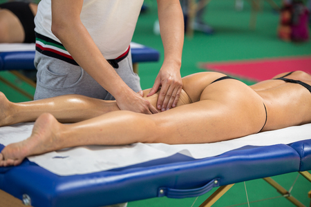 Athletes Thigh Muscle Professional Massage Treatment after Sport Workout Fitness and Wellness. Stock Photo