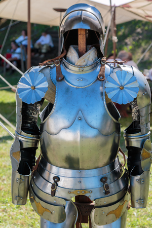 Medieval Metallic Armor with Helmet near White Tent.