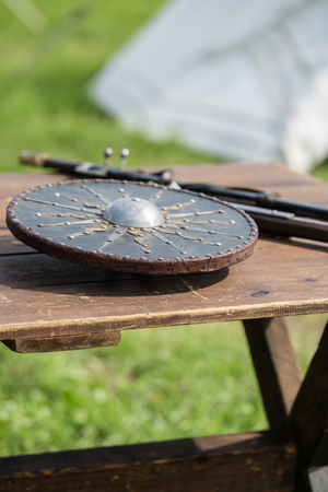 Circular and Metallic Shield on Wooden table: Medieval Metallic Armors and Weapons.